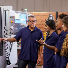 students and teacher looking at a CNC machine
