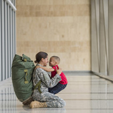 female military hugging son