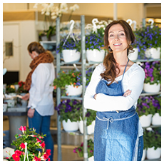 Portrait of smiling mid adult female owner with customers in background at flower shop