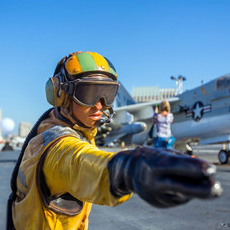 military person on deck of an aircraft carrier directing planes