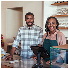 Portrait of two young African entrepreneurs smiling and standing welcomingly together behind the counter of their trendy cafe